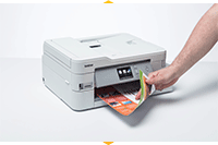 Hand taking colourful document from MFC-J1300DW printer