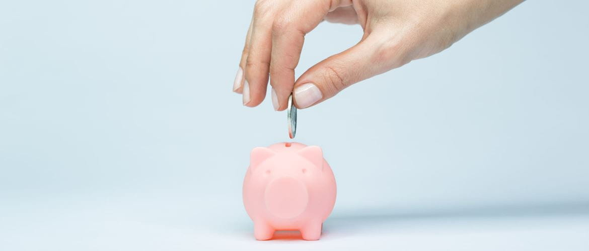 hand places coin into tiny piggy bank