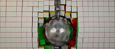 wrecking ball crashes into wall of white and coloured bricks