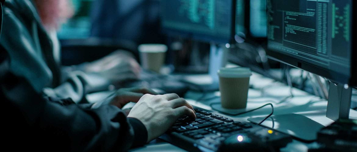 Close-up Shot of Hacker using Keyboard. There is Coffee Cups and Computer Monitors with Various Information