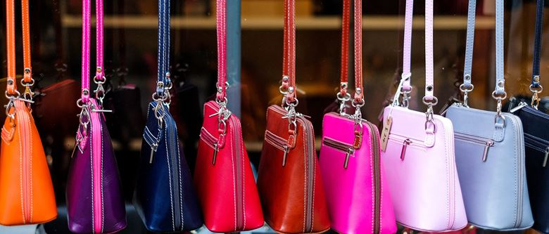 a row of colourful leather handbags for sale
