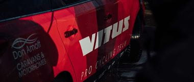 Vitus logo on the side of a cycling support vehicle