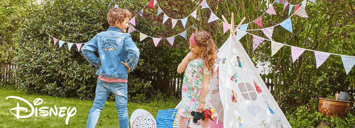 Two kids standing in front of Disney embroidered tent in garden